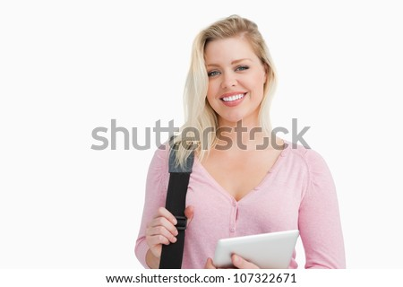 Blonde woman holding a tablet computer and a shoulder bag against a white background - stock photo
