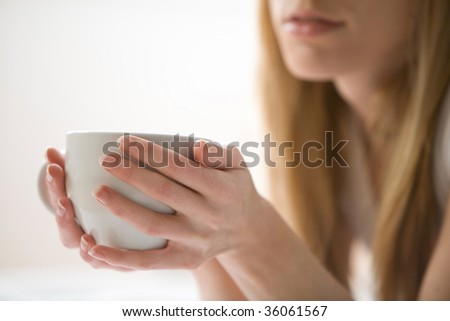 Blonde woman holding a white mug - stock photo