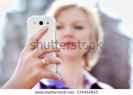 Blonde woman holding smartphone and reading news - stock photo