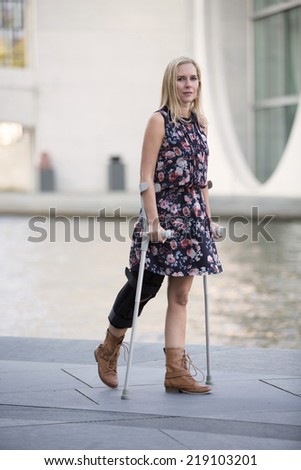 blonde woman in a dress walking with crutches - stock photo