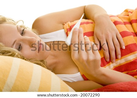 Blonde woman in bed with clinical thermometer - stock photo