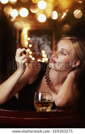 Blonde woman in black dress with glass whisky against lights - stock photo