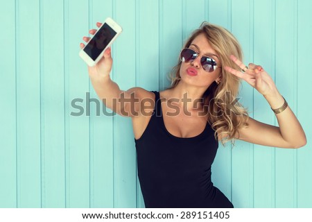 blonde woman in bodysuit with perfect body taking selfie with smartphone  toned instagram filter - stock photo