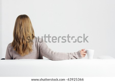 Blonde woman in gray sweater sitting on sofa in front of empty wall - stock photo