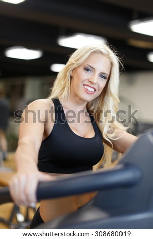 Blonde woman in gym on treadmill, teeth smile, indoor portrait