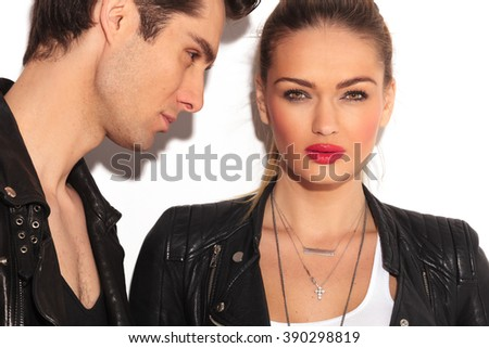 blonde woman in leather jacket looks to  the camera while her boyfriend is looking at her; closeup picture of a young couple in leather jackets - stock photo