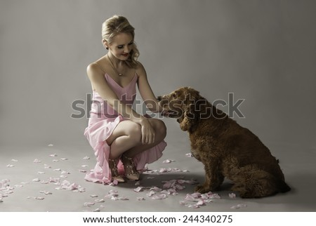 Blonde woman in pink petting her adorable dog, seated on the floor amongst pink rose petals. - stock photo