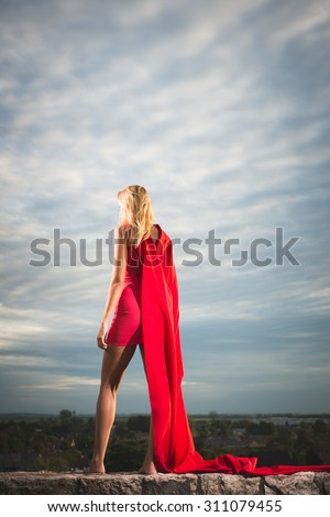 Blonde woman in red dress standing over the city and looking away - stock photo