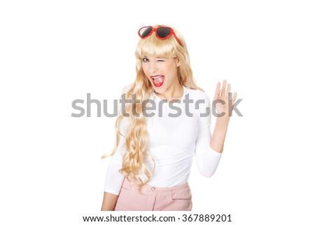 Blonde woman in sunglasses blinks eye. - stock photo