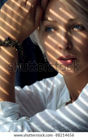Blonde woman in the sunlight looking through jalousie - stock photo