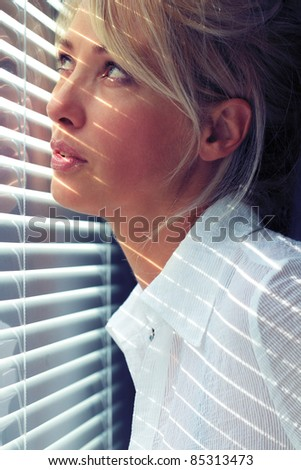 Blonde woman in the sunlight through jalousie - stock photo