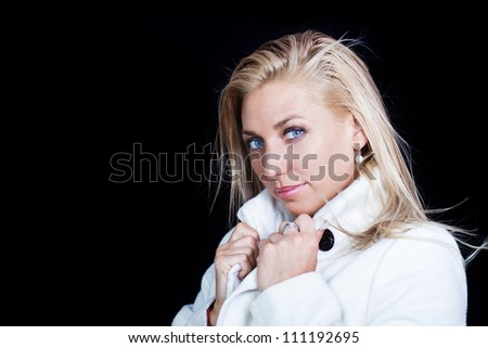 blonde woman in white coat - on black background - stock photo