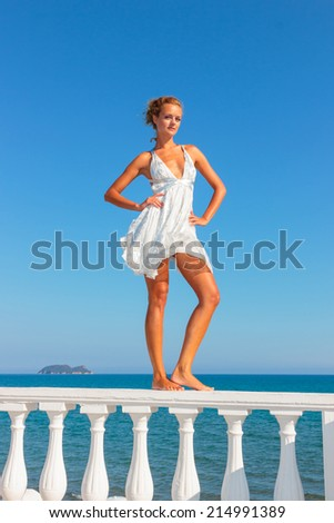 Blonde woman in white dress by the sea in the summer time - stock photo