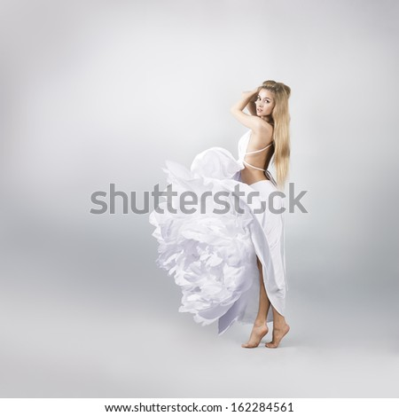Blonde Woman in White Peony Flower Dress on Gray Background - stock photo