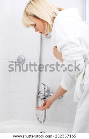 Blonde woman is going to take a bath. - stock photo