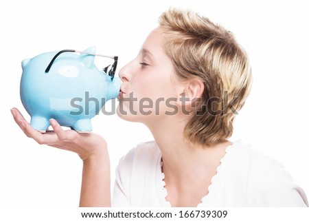 blonde woman kissing a piggy bank which is wearing glasses on white background - stock photo