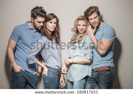 blonde woman laughing while standing among her friends. casual group of people against gray studio wall - stock photo