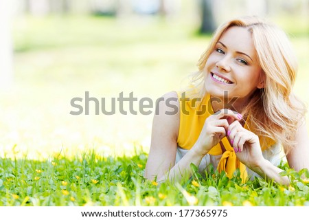 Blonde woman laying on the grass and smiling - stock photo