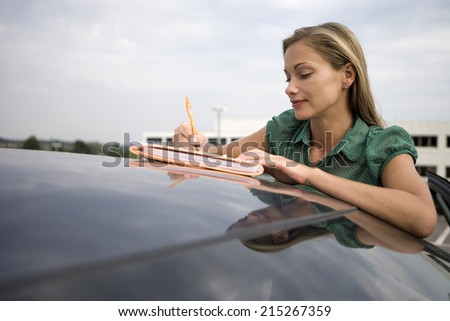Blonde woman leaning on stationary car roof, writing on piece of paper in folder, smiling - stock photo