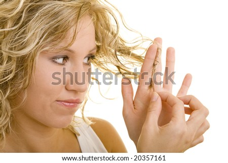 Blonde woman looking at her hair - stock photo
