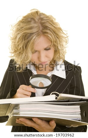 Blonde woman looking through a magnifying glass - stock photo