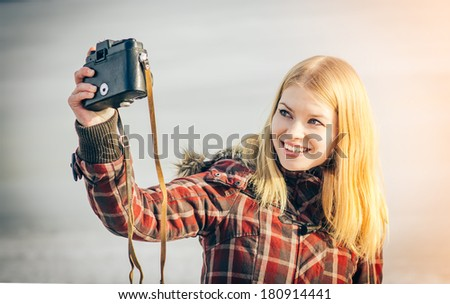 Blonde Woman making self shot on her vintage retro camera happy smiling hipster Lifestyle winter time - stock photo