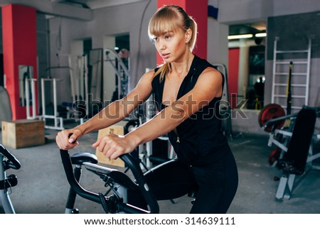blonde woman on exersizing bike, doing workout in the gym - stock photo