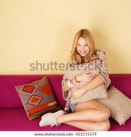 Blonde woman on purple couch. Pretty young woman relaxing on a sofa at home. Girl in living room. Beautiful cheerful woman on the sofa  - stock photo