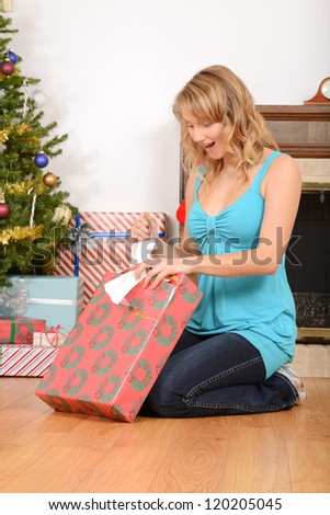 Blonde woman opening christmas present - stock photo