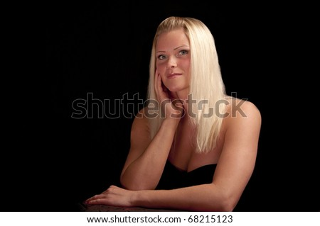 blonde woman photographed against a black background - stock photo