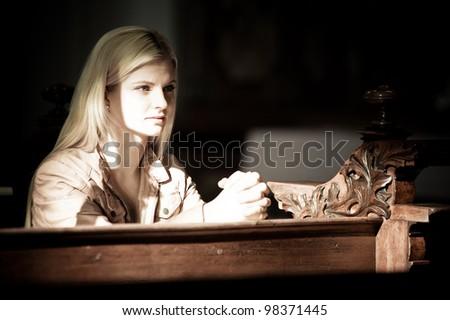 Blonde Woman Praying inside of a Church - stock photo