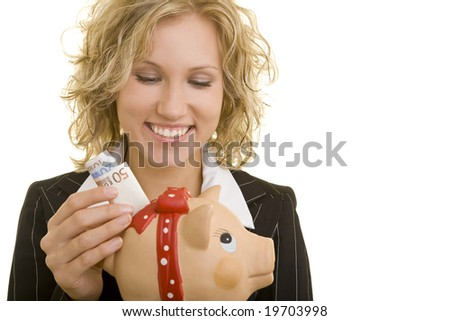 Blonde woman putting money in a piggy bank - stock photo