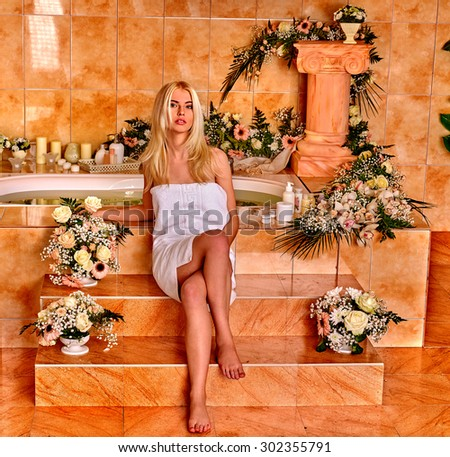 Blonde woman relaxing at flower water spa. - stock photo