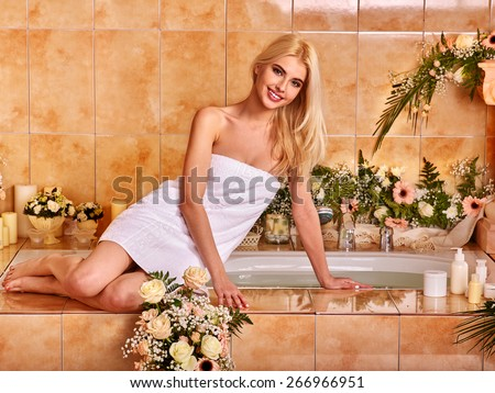 Blonde woman relaxing at flower water spa. Rose petal in hand. - stock photo