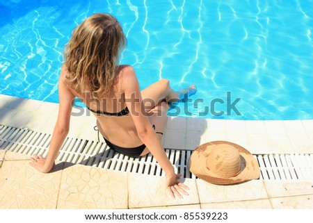 Blonde woman relaxing by the pool - stock photo