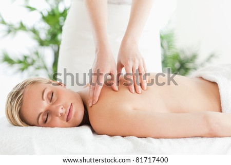 Blonde woman relaxing on a lounger during massage in a wellness center