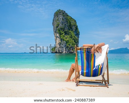 Blonde woman relaxing on the beach in Thailand - stock photo