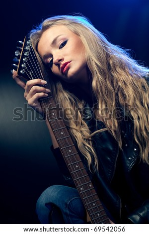 blonde woman rock star portrait with guitar - stock photo