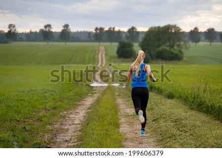 Blonde woman running in nature - stock photo