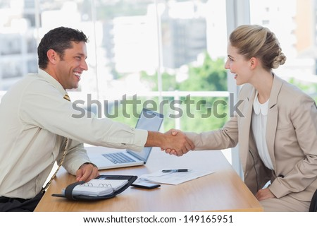 Blonde woman shaking hands while having an interview in office - stock photo