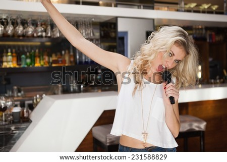 Blonde woman singing and dancing with hand up at the nightclub - stock photo
