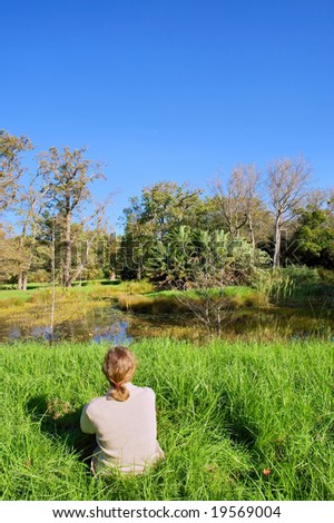 Blonde woman sits next to small pond in park. Shot in Vergelegen estate, near Cape Town, Western Cape, South Africa. - stock photo