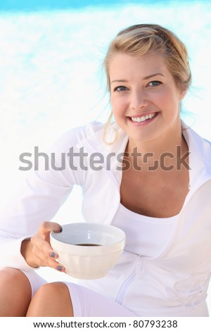 blonde woman sitting and drinking a coffee bowl - stock photo