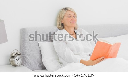 Blonde woman sitting in bed reading orange book at home - stock photo