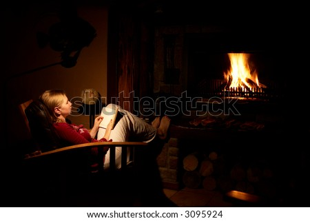 Blonde woman sitting infront of the fireplace, reading the book and thinking. - stock photo