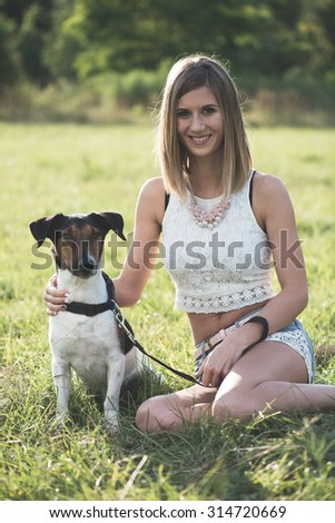 Blonde woman sitting with a cute terrier dog outdoor in the park.