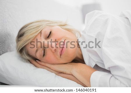 Blonde woman sleeping peacefully at home in bed