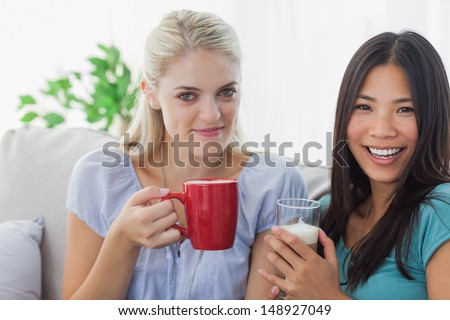 Blonde woman smiling at camera with friend at home on couch
