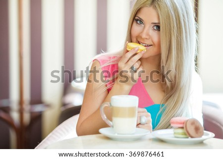 blonde woman smiling. woman portrait. beautiful young girl in cafe. coffee latte and cookies macarones. woman in face alone.Charming woman in a restaurant  - stock photo