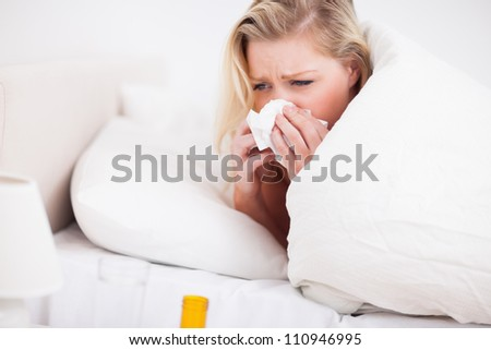 Blonde woman sneezing in her bed - stock photo